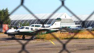 Flygplan bakom ståltrådsstaket.