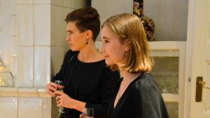 Två svartklädda kvinnor håller i var sitt skumvinsglas.