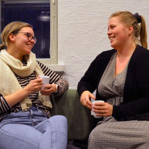 Två unga kvinnor sitter och dricker kaffe på en soffa framför en vägg.