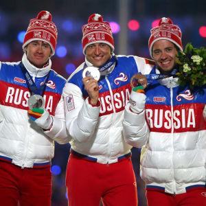 De ryska medaljörerna på femmilen i Sotji poserar på prispallen.