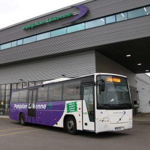 En lila och vit buss som står på en busstation. I bakgrunden en stor grå byggnad.