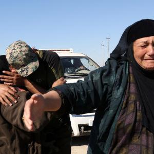 En irakisk polis kramar sin mor som nyss har flytt den befriade förorten Gagjali öster om Mosul.