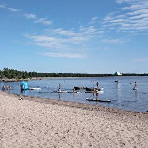 En badstrand en somrig dag. Människor ligger i sanden, badar i havet och åker på sup-brädor i vattnet. I havet skymtar en vattenkarusell.