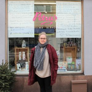 Kvinna utanför affär med stora handskrivna skyltar i fönstret