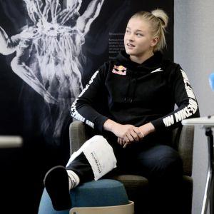Wilma Murto sitter i en stol och håller sitt opererade knä på en pall