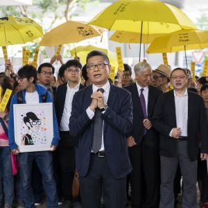 Professor Chan Kin Man som grundade ockupationsrörelsen år 2014 fick stöd av ett hundratal aktivister med gula paraplyer då han kom till domstolsbyggnaden i Hongkong
