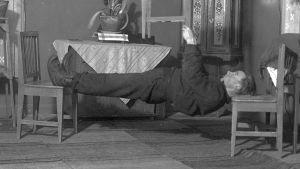 """En man leker """"ligga lik"""", där man ska hålla kroppen så styv som möjligt medan man ligger mellan två stolar. Bilden är tagen 1937 i Närpes, Kalaks."""