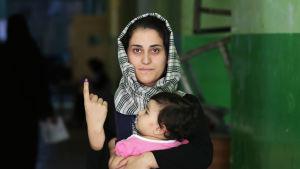 En afghansk kvinna visar upp sitt bläckmarkerade finger efter att ha röstat i Kabul på lördagen.