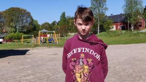 En pojke står på en tom skolgård.