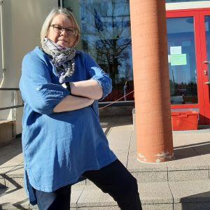 Kvinna med grått hår och glasögon och blå tröja står med armarna i kors på en skoltrappa.