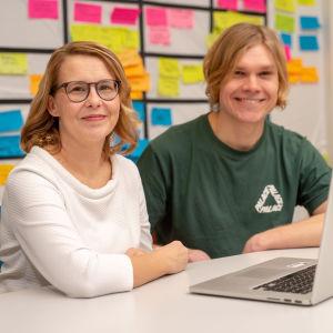 Eija Moisala ja Lauri Mikola istuvat työpöydän ääressä tietokone edessään.