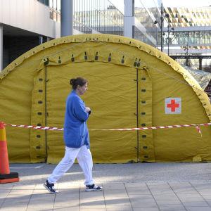 Ett gult tält utanför Karolinska universitetssjukhuset och en sjukskötare som går förbi.
