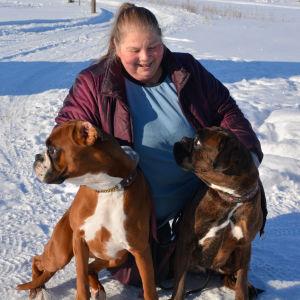 Kvinna i snö med två hundar framför sig