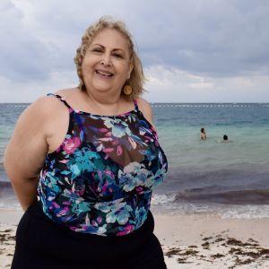En kvinna i baddräkt ler in i kameran. I bakgrunden simmar hennes väninnor i ett tångfyllt hav.