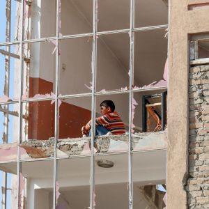 Pojke sitter i ett hus som skadats av en bilbomb. Kabul 13.11.2019