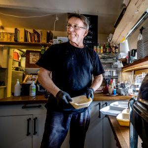 En man lagar take away portioner i ett café