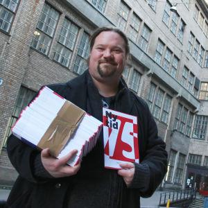 Ny Tids chefredaktör Janne Wass håller i en bunt tidskrifter utanför kabelfabriken i Helsingfors.