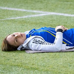 Linda Sandblom ligger på gräset och koncentrerar sig.