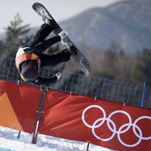 Peetu Piiroinen tekee voltin, takana aita, jossa olympiarenkaat.