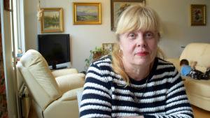 Kerstin Karlberg sitter vid ett köksbord. I bakgrunden syns ett vardagsrum.