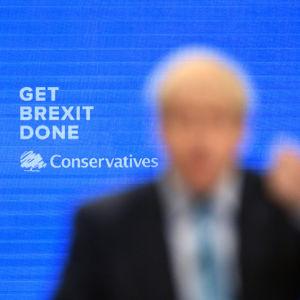 I bakgrunden testen: GET BREXIT DONE underskrivet av Conservatives. I förgrunden en helt suddig Boris Johnson som gestikulerar.