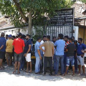 Människor samlas utanför en byggnad efter bombattentat i Sri Lanka