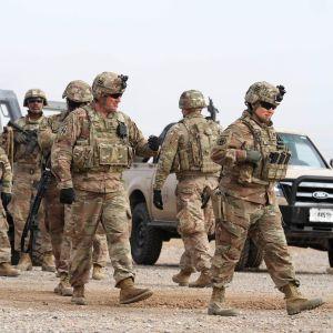 Joukko yhdysvaltalaissotilaita kävelee maastoautojen editse.