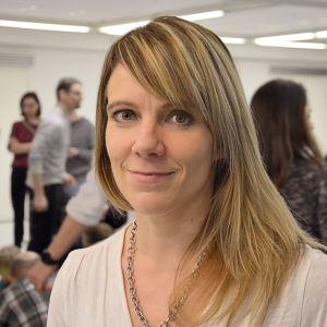 Linda Mannila med ett undervisningsutrymme i bakgrunden.