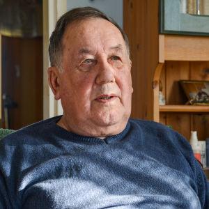 Närbild på en äldre man i blå skjorta som sitter i en stol i sitt vardagsrum.