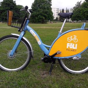 En blågul eFölläri-cykel står på en gräsmatta.