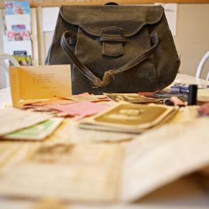 Innehållet i en brun sliten handväska ligger utspritt på ett köksbord. Där finns fotografier, ransoneringskort och en bröllopsinbjudan.
