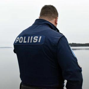 En polis med ryggen mot bilden, stilla hav i bakgrunden.