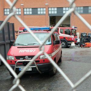 Brandbil framför röd industrifastighet.