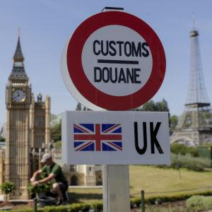 Britannian ja EU:n välistä tullirajaa esittävä liikennemerkki, taustalla Britannian parlamenttitalon pienoismalli.