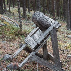 Puinen taideteos, pää ja giljotiini, teksti Korpilaki