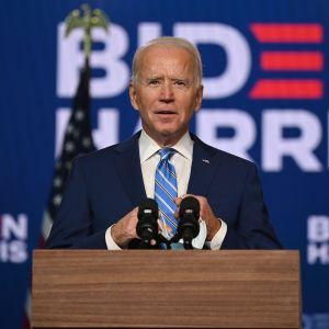 Joe Biden vid ett podium. Han tittar uppåt och ser hoppfull men bestämd ut.