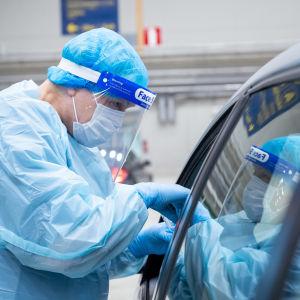 En skötare i skyddsutrustning tar coronatest av en person i en bil.