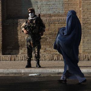 Afganistanilainen sotilas seisoo vartiossa kadulla.