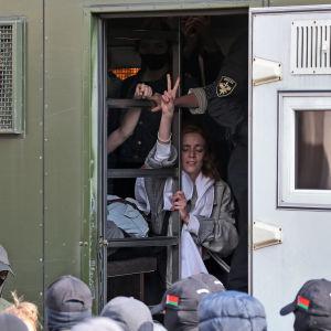 Genom dörren till ett polisfordon syns en kvinna som visar peace-tecknet.