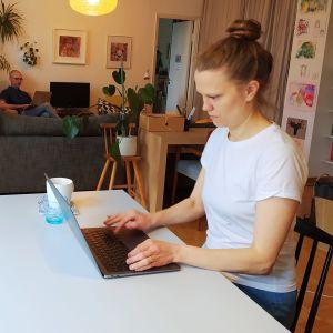 Kvinna i förgrunden skriver på bärbar dator, man i bakgrunden jobbar också på dator sittandes i en fåtölj.