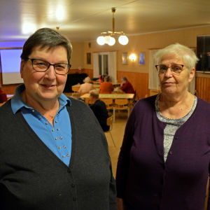 Två kvinnor står i dörröppningen till en stor sal där människor sitter runt bord.