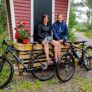 En man och en kvinna sitter på en trätrappa med varsin terrängcykel framför sig.