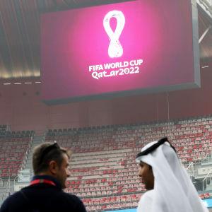 Två personer står inne i en tom arenan, på bildskärmen syns logon för VM 2022.