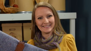 Hymyilevä nainen askarteluhuoneessa