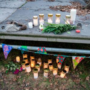 Ljus och blommor på en liten scen, i ett höstigt landskap. Ser ut som ett minnesmärke för någon som dött.