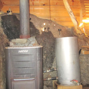 Sauna on rakennettu kallion koloon, kolmella sivulla kalliota. Yläosan hirret on kierrätys tavaraa.