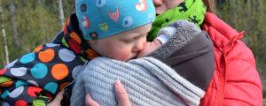 Ett litet barn pussar sitt babysyskon. De sitter båda i sin mammas famn.