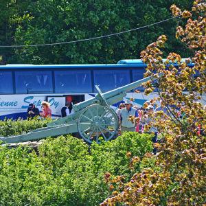 Människor och kanon framför buss