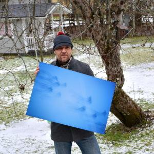 Fotograf står ute med sin bild i famnen.