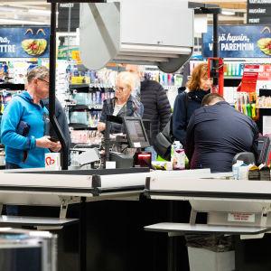 Kunder i butikskassor i mataffären.